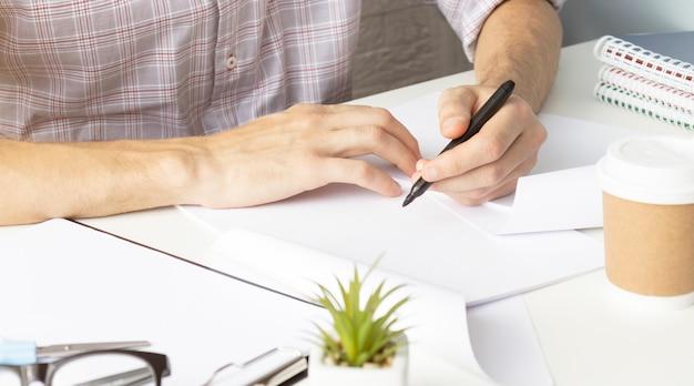 Sluit omhoog van de handen van de vrouw die in spiraalvormige blocnote schrijven die op houten desktop met diverse punten wordt geplaatst