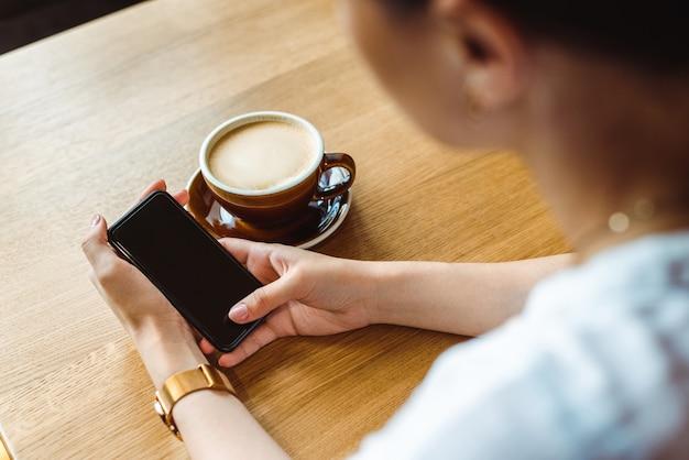 Sluit omhoog van de handen van de vrouw houdend celtelefoon met lege exemplaar ruimtepuinkegel voor uw reclametekstbericht of promotionele inhoud
