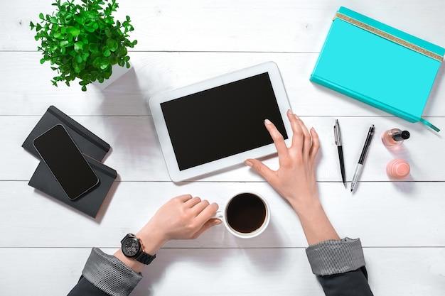 Sluit omhoog van de handen van de vrouw met lange vingers die tablet houden. smartphone en notebook liggen op tafel. bovenaanzicht. ruimte kopiëren
