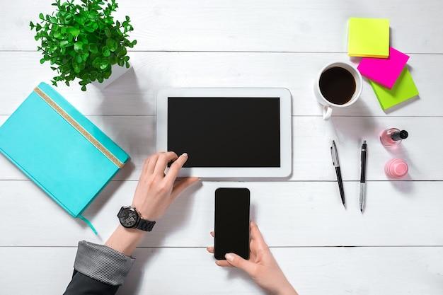 Sluit omhoog van de handen van de vrouw met lange vingers die tablet houden. smartphone en notebook liggen op tafel. bovenaanzicht.