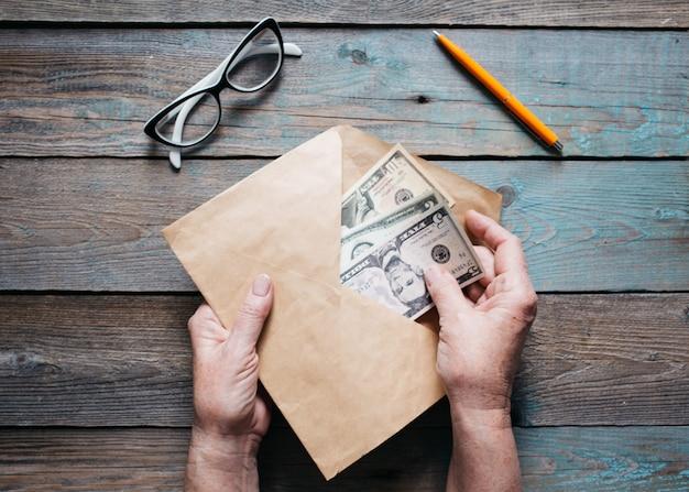 Sluit omhoog van de handen van de vrouw zet amerikaanse dollarrekeningen in een envelop op houten desktop