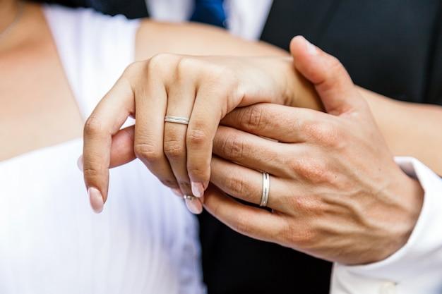 Sluit omhoog van de handen van een enkel echtpaar dat hun ringen in hun huwelijksdag toont