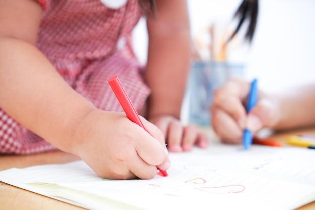 Sluit omhoog van de handen van een klein kindtekening met kleurpotlood.