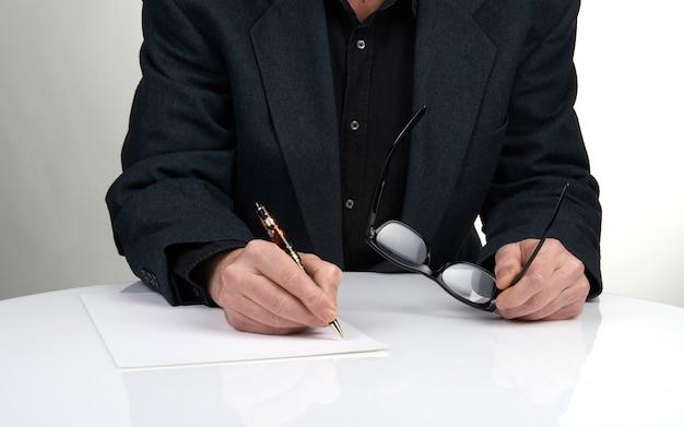 Sluit omhoog van de handen van een zakenman in een kostuum ondertekening of het schrijven van een document op een blad