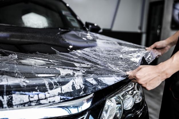 Sluit omhoog van de installatie van de verfbeschermingsfilm op voorbumper van moderne luxeauto. ppf is een polyurethaanfilm die op het auto-oppervlak wordt aangebracht om de lak te beschermen tegen steenslag, spetters en slijtage