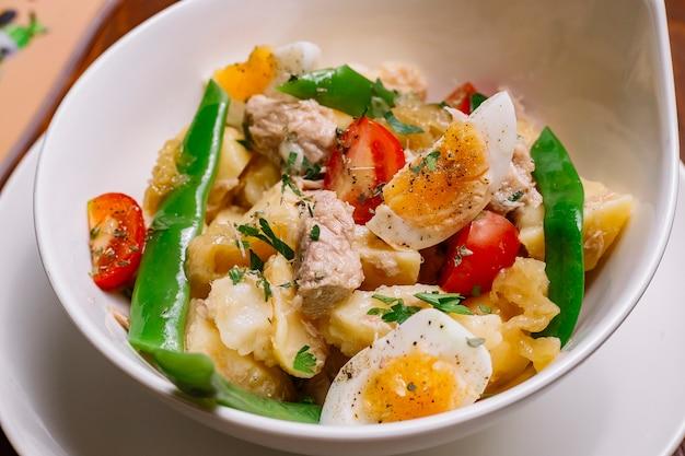 Sluit omhoog van de italiaanse kom van de aardappelsalade met van de de kersentomaat van tonijnbonen de peterselie gekookte eieren en olijfolie