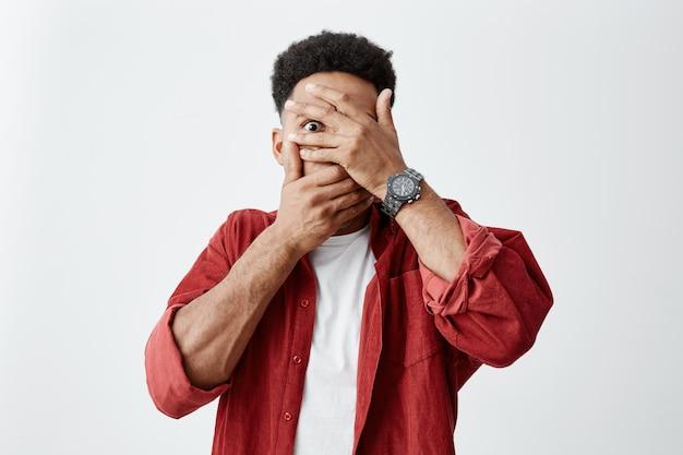 Sluit omhoog van de jonge donkerhuidige mens met afrokapsel in wit e-shirt onder het rode gezicht van de overhemdskleding met handen, kijkend door vingers met doen schrikken gezichtsuitdrukkingen.