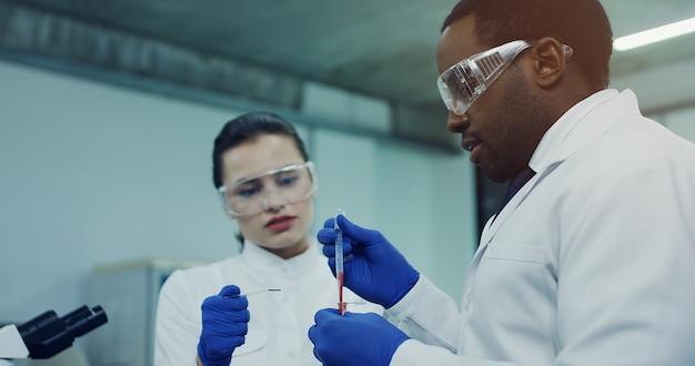 Sluit omhoog van de kaukasische jonge vrouw en de afrikaanse amerikaanse man in glazen die bloedonderzoek samen in buizen in de laboratoriumruimte doen.