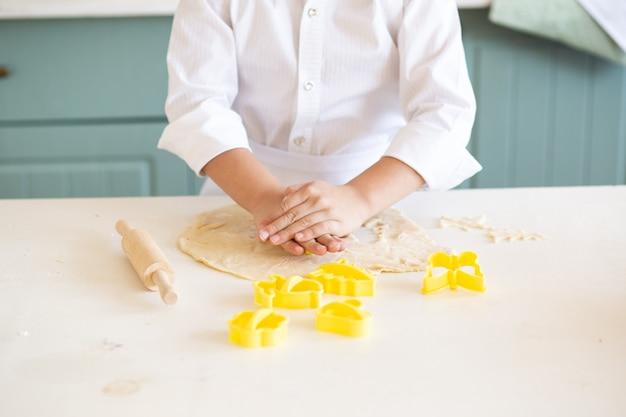 Sluit omhoog van de koekjes van het jongensbaksel in keuken