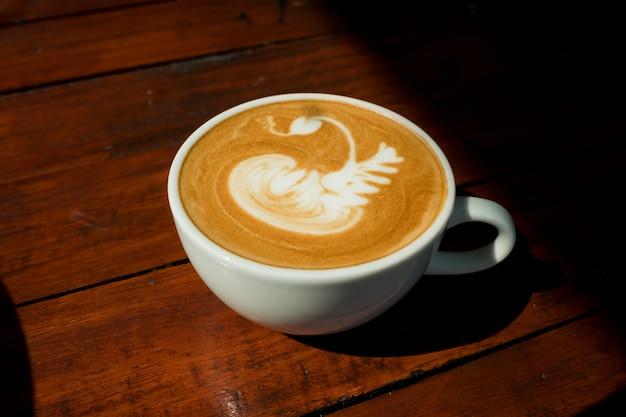 Sluit omhoog van de koffie van de lattekunst in witte kop