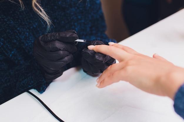 Sluit omhoog van de manicure van procesfrankrijk bij schoonheidssalon.