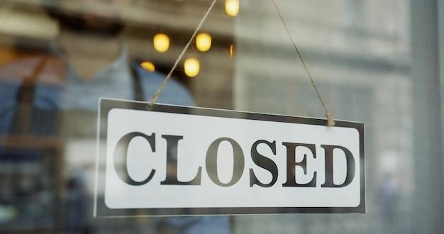 Sluit omhoog van de mannelijke kaukasische handen draaiend een uithangbord op de glasdeur van de winkel van gesloten om te openen en mens die in glazen uit op straat kijkt.