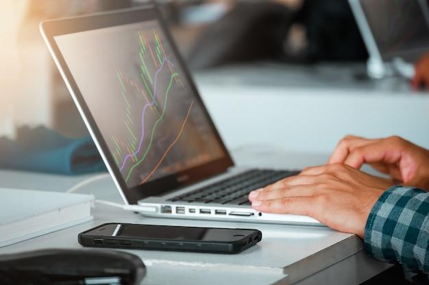 Sluit omhoog van de mens die laptop de markt van de handelsbeurs in koffiekoffie met behulp van