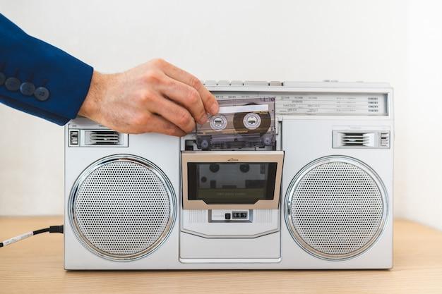 Sluit omhoog van de mens gebruikend een oude radio binnen.