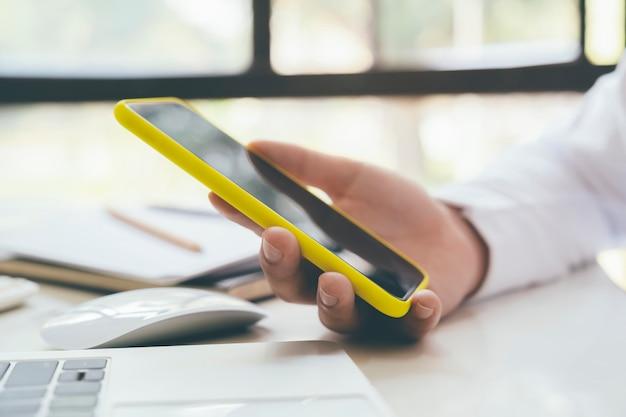 Sluit omhoog van de mens gebruikend mobiele telefoon.