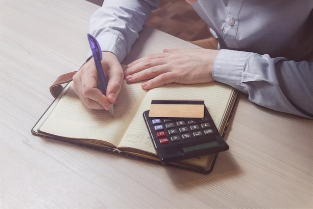 Sluit omhoog van de mens met calculator tellend geld en thuis het maken van nota's