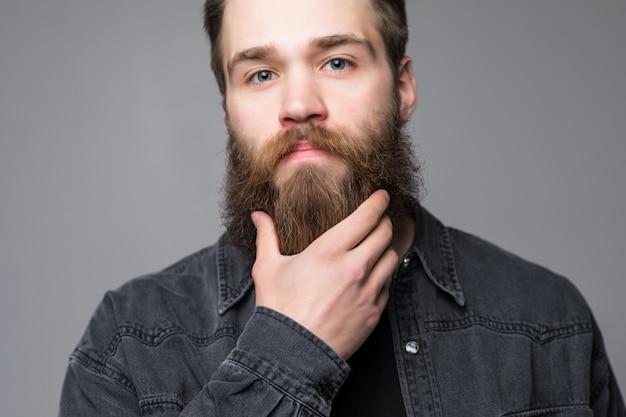 Sluit omhoog van de mens raak zijn lange die baard en snor op grijze achtergrond wordt geïsoleerd