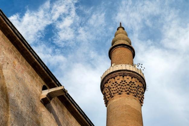 Sluit omhoog van de minaret van de grote moskee van bursa met blauwe hemel.