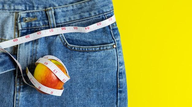 Sluit omhoog van de rode appel op jeans die rond een meetlint, een gezondheid en op dieet zijn concept wordt verpakt