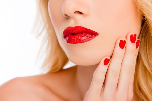 Sluit omhoog van de rode lippen van de grote vrouw en hand met rode manicure
