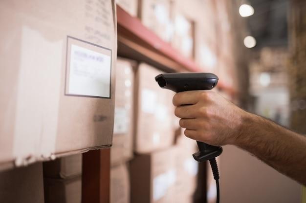 Sluit omhoog van de scanner van de arbeidersholding in pakhuis