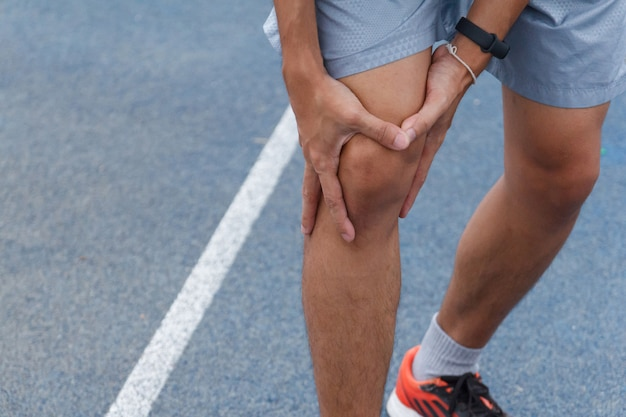 Sluit omhoog van de sportmens die met pijn op sporten lijden die knieblessure na het lopen lopen. verwonding van trainingconcept.