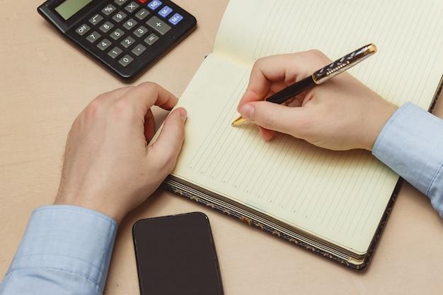 Sluit omhoog van de toevallige mens die op document notitieboekje of oude agenda schrijven