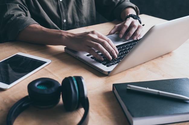 Sluit omhoog van de toevallige mens thuis gebruikend laptop op het bureau.