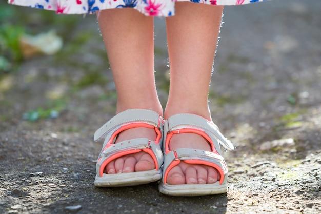 Sluit omhoog van de voeten van het kindmeisje die de schoenen van de zomersandals dragen