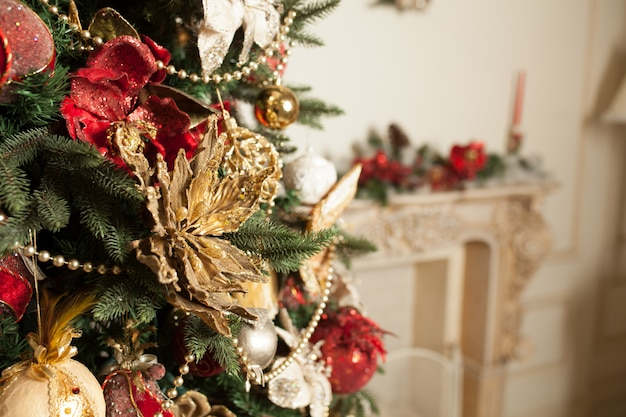Sluit omhoog van decoratierood en goud verfraaid op groene kerstmisboom of pijnboom