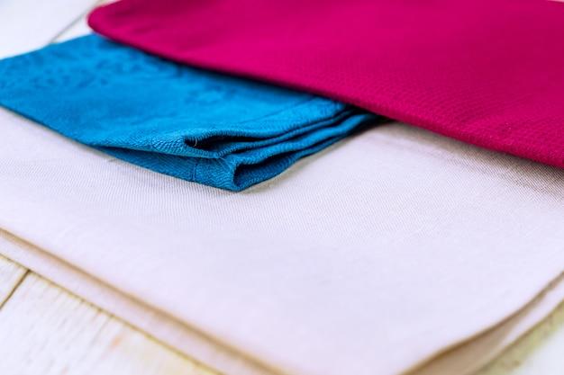 Sluit omhoog van doekservetten van beige, blauwe en de kleuren van bourgondië op rustieke witte houten lijst.