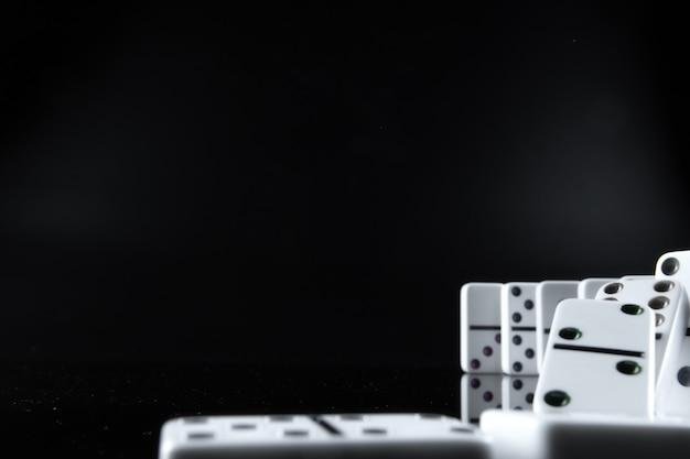 Sluit omhoog van dominostukken op zwarte achtergrond