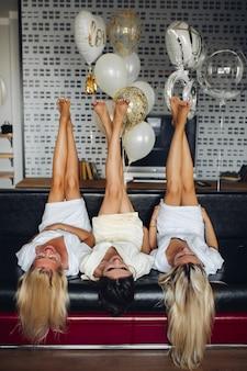 Sluit omhoog van drie paren vrouwelijke benen met pedicure in lucht.
