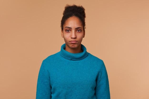 Sluit omhoog van droevig jong afrikaans amerikaans meisje dat een blauwe sweater draagt, met donker krullend haar. kijkend naar de camera die zijn lippen laat vallen die over beige achtergrond worden geïsoleerd.