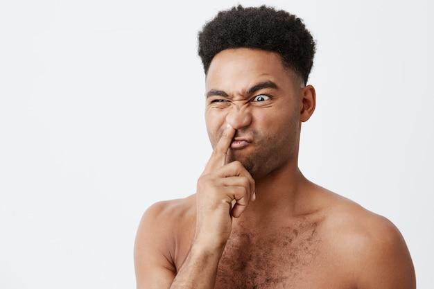 Sluit omhoog van dwaze mooie donkerhuidige amerikaan met afrokapsel en naakte lichaamshoudende vinger in neus, opzij kijkend met stomme gezichtsuitdrukking, die op zijn vn in de ochtend zijn.