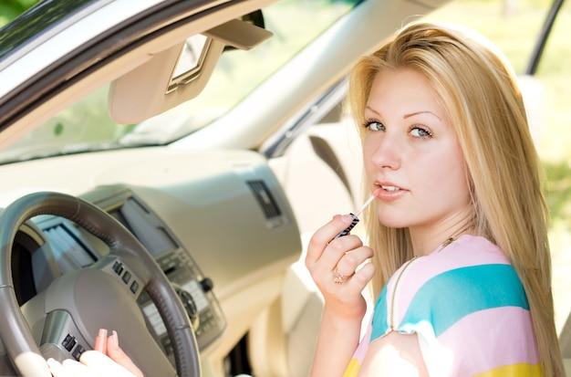 Sluit omhoog van een aantrekkelijk blond meisje dat lipgloss toepast die de camera bekijkt.