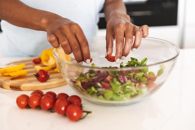 Sluit omhoog van een afro-amerikaanse vrouw die een salade maakt