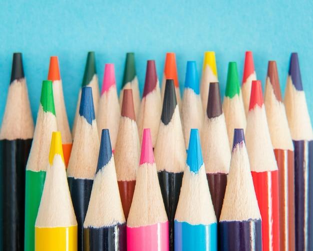 Sluit omhoog van een assortiment van kleurenpotloden op blauw