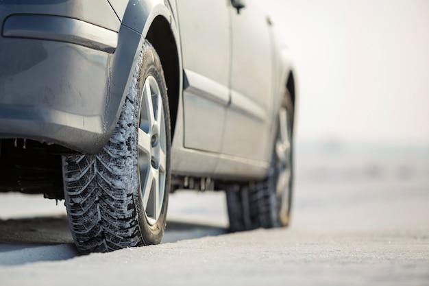 Sluit omhoog van een autoband die op sneeuwweg op de winterdag wordt geparkeerd. transport en veiligheidsconcept.