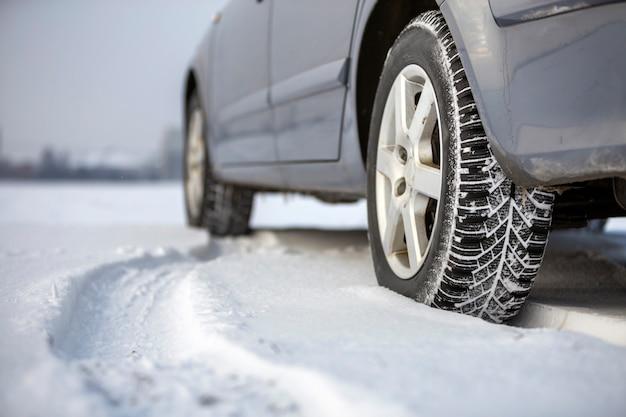 Sluit omhoog van een autoband op sneeuwweg op de winterdag wordt geparkeerd die. transport- en veiligheidsconcept.