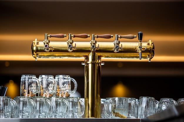 Sluit omhoog van een biertapkraan of kraan met enorme arrenge van lege glazen in de bar of pub, restaurantconcept