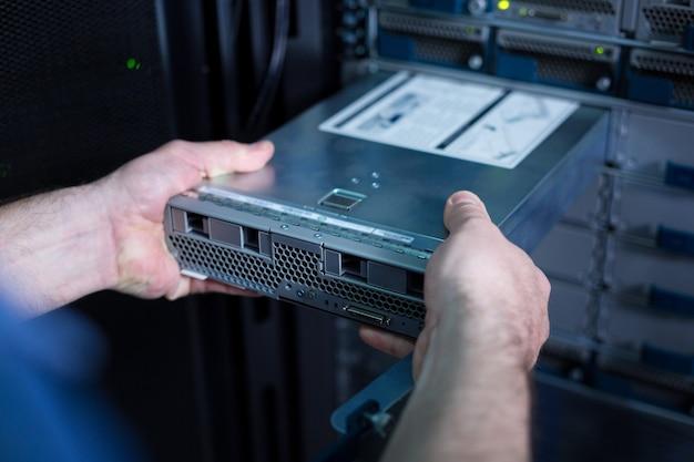 Sluit omhoog van een bladeserver die door een professionele bekwame mannelijke technicus in het serverrek wordt geplaatst
