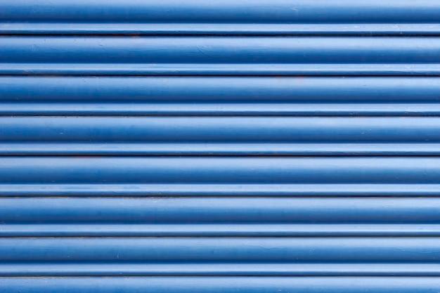 Sluit omhoog van een blauw metaalgordijn dat een gesloten winkel of een huis beschermt