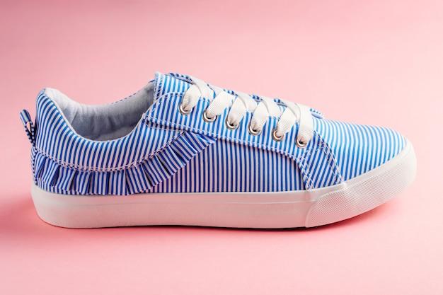 Sluit omhoog van één blauwe gestreepte vrouwelijke tennisschoen op een roze achtergrond.