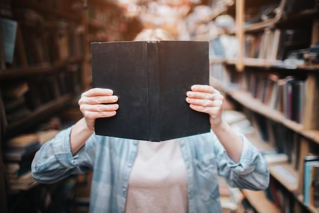 Sluit omhoog van een blondemeisje dat een boek houdt en haar gezicht ermee sluit. jonge vrouw staan tussen grote planken met boeken en tijdschriften.