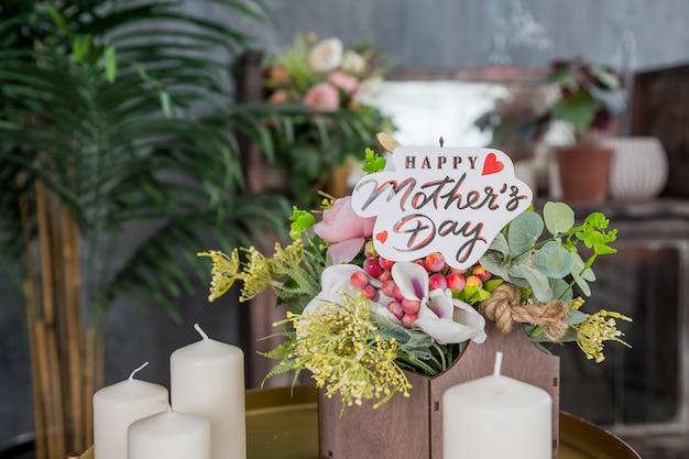 Sluit omhoog van een boeket van roze rozen met een gelukkige moederdagkaart op vage achtergrond. moederdagachtergrond. bloemen op speciale dag. kaarsen en bloemen.