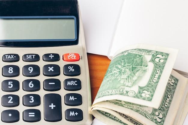 Sluit omhoog van een calculator en muntstukken op een bedrijfsachtergrond