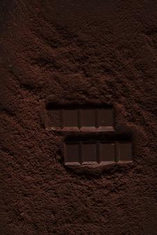 Sluit omhoog van een chocoladestuk in chocoladepoeder op een lijst