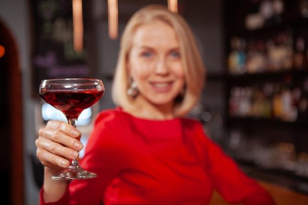 Sluit omhoog van een cocktail steunt de gelukkige elegante vrouw aan de camera