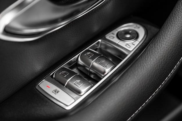 Sluit omhoog van een deurcontrolebord in een nieuwe moderne auto. armleuning met vensterbedieningspaneel